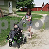 Rob Winner – rwinner@shawmedia.com<br /> <br /> Tino Camero, 10, is pushed by his sister, Tia Camero, 13, outside their home in Sycamore, Ill., Monday, June 3, 2013. Amie Camero, Tino's mother, is unable to provide a new wheelchair ramp for Tino and is hoping for donations to help pay for construction of a new ramp.
