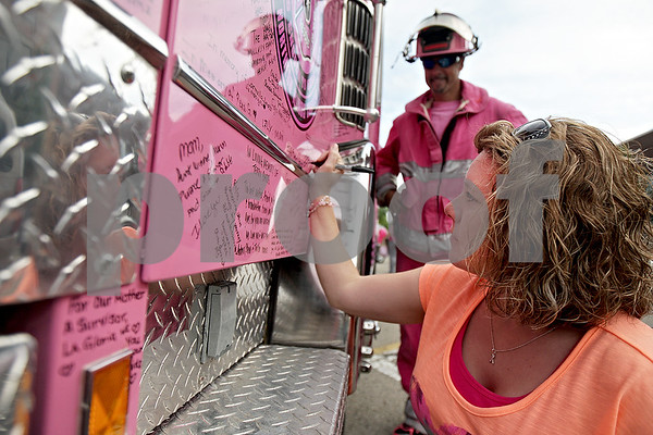 Monica Maschak - mmaschak@shawmedia.com<br /> Clarice Pepper, 33, of Kirkland, signs Jessica, the pink fire truck, in honor of her aunt Sarah who passed from breast cancer at the ninth annual Ladies Night Out event for breast cancer awareness in downtown Sycamore on Thursday, July 6, 2013. Jessica, with the Northern Illinois Chapter of Pink Heals, was driven down from McHenry to be at the event. There are now 80 fire trucks like Jessica around the country spreading education, awareness and support for breast cancer.