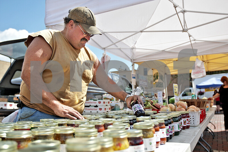 Monica Maschak - mmaschak@shawmedia.com<br /> Bryan Crump, of Crump Family Gardens in Carlock, resorts jars of jam and salsa at the farmers market held in the Van Buer Plaza in Downtown Dekalb on Thursday, June 13, 2013. Crump's stand accepts the voucher given seniors and low-income families by a KishHealth System to use at local farmers markets.