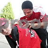 Monica Maschak - mmaschak@shawmedia.com<br /> Freshman Defensive Tackle Mario Jones signs a T-shirt on eight-year-old Mallory Armstrong's back during the Northern Illinois University Night in downtown Sycamore on Tuesday, June 11, 2013. The event was part of Sycamore's monthly Tuesdays on the Town. About 20-30 NIU athletes hung out with kids, shot hoops and signed autographs.