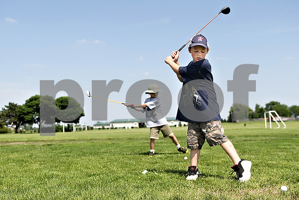 Monica Maschak - mmaschak@shawmedia.com<br /> Royce Gradls (left), 6, and Kyle Prebil, 6, of Sycamore, practice their golf swing at Sycamore Community Park on Friday, June 14, 2013. The boys took advantage of clear skies and a temperature of 77 degrees Fahrenheit.