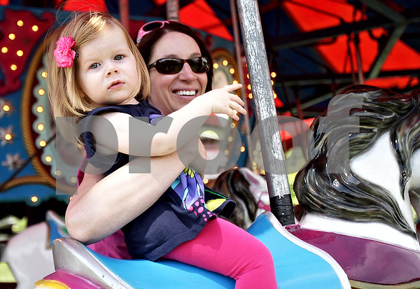 Monica Maschak - mmaschak@shawmedia.com<br /> Addison Andrus, 1, rides the carousel with her mom, Ellen Andrus, at the Malta Days festival at Lions Park on Saturday, June 8, 2013.