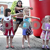 Monica Maschak - mmaschak@shawmedia.com<br /> Bella Jacobs, 4, Kira Collins, 6, and Vivianne Moyer, 3, learn a cheer from Northern Illinois University Cheerleader Kacie Patterson during the NIU Night in downtown Sycamore on Tuesday, June 11, 2013. The event was part of Sycamore's monthly Tuesdays on the Town. About 20-30 NIU athletes hung out with kids, shot hoops and signed autographs.