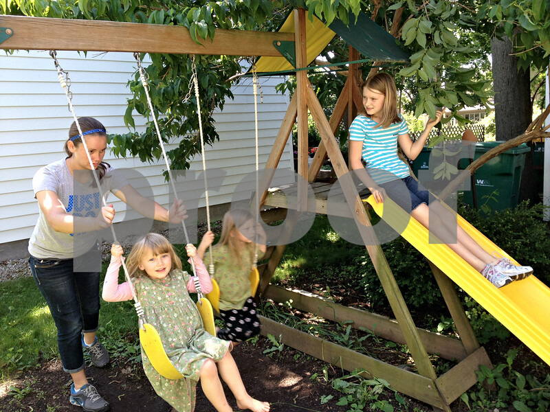 Stephanie Hickman – shickman@shawmedia.com<br /> <br /> Jillian Diehl pushes four-year-old Aubrey Holseberg on the swing as she babysits her and her sisters, Claudia, 6, and Natalie, 9, on Friday, June 14. Diehl, 15, babysits the Holseberg girls once a week during the summer.