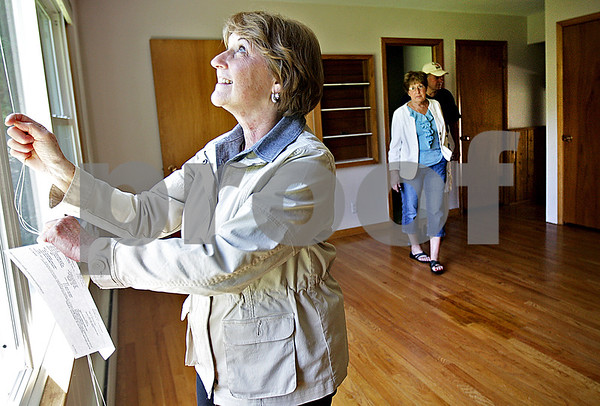 Monica Maschak - mmaschak@shawmedia.com<br /> Realtor Sharon Rhoades, with McCabe Realtors, opens blinds in a room as she shows a home to DeKalb couple Phyllis and Dan Anderson on Friday, June 7, 2013. This was the second visit to this home for the Andersons, who are looking to move into a ranch home in the DeKalb area.