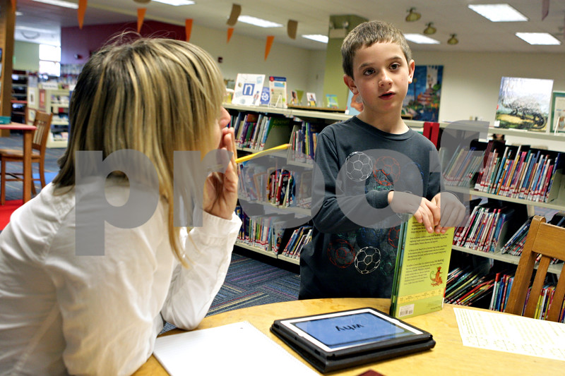 Rob Winner – rwinner@shawmedia.com<br /> <br /> Tutor Jill Metcalf (left) quizzes Jaden Cochran, 7, during a visit to the Sycamore Public Library on Friday morning. Metcalf brought Cochran to register for the library's summer reading program.<br /> <br /> Friday, June 7, 2013<br /> Sycamore, Ill.