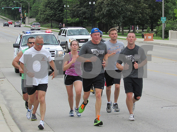 Police officers with the City of DeKalb, Sycamore, Northern Illinois University, and the DeKalb County Sheriff run down Lincoln Highway as a part of the Illinois Law Enforcement Torch Run for the Special Olympics. The torch will eventually make its way to Bloomington, the site of this year's Summer Games.