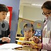 Rob Winner – rwinner@shawmedia.com<br /> <br /> Gladys Bisco (right) looks through the summer program registration binder at the Children's Desk at the Sycamore Public Library for a craft or workshop for her children, Nathaniel (left), 11, and Henry, 7, to participate in after both completed a goal as part of the library's summer reading program.<br /> <br /> Friday, June 7, 2013<br /> Sycamore, Ill.