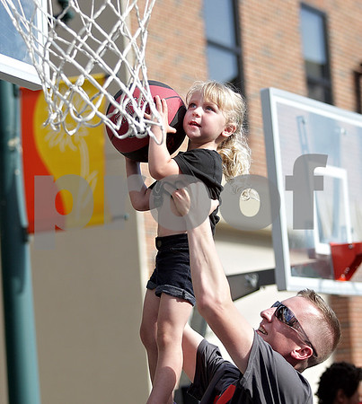 Monica Maschak - mmaschak@shawmedia.com<br /> Adam Lang, of Genoa, lifts up daughter Sadie Lang, 3, so she can dunk the basketball during the Northern Illinois University Night in downtown Sycamore on Tuesday, June 11, 2013. The event was part of Sycamore's monthly Tuesdays on the Town. About 20-30 NIU athletes hung out with kids, shot hoops and signed autographs.