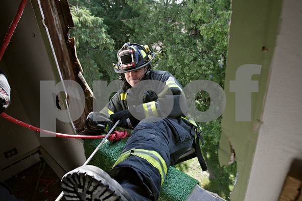 Rob Winner – rwinner@shawmedia.com<br /> <br /> DeKalb firefighter Greg Thornton practices bailing out of a second floor window during a training exercise at an empty house located on Hollister Avenue in DeKalb, Ill., Wednesday, June 19, 2013.