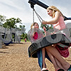 Monica Maschak - mmaschak@shawmedia.com<br /> Erin Templin (left), 9, and Kaiylee Mecklenburg, 10, of Sycamore, share the tire swing at Hopkins Park playground in DeKalb after spending the day at a pool on Monday, June 17, 2013.