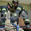 "Rob Winner – rwinner@shawmedia.com<br /> <br /> Firefighters Steve Cruz (left) and Joe Wempe (right) pull a dummy up from the basement to the first floor during a training exercise at an empty house on Hollister Avenue in DeKalb, Ill., Wednesday, June 19, 2013. ""This is brute strength. This is busting your butt and getting him out."" said DeKalb Assistant Chief Jeff McMaster (center)."
