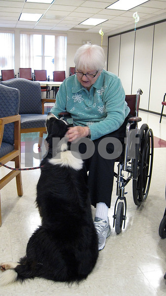 Cleo Macart, a resident of the DeKalb County Nursing & Rehab Center, pets Abbie, a Border collie owned by Connie Seraphine. Abbie is one of eight dogs that visit local nursing homes through TAILS Humane Society's Pawsitive TAILS program.