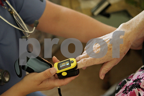 Rob Winner – rwinner@shawmedia.com<br /> <br /> Registered nurse Tanya Diedrich (left), of DeKalb County Hospice, checks Jocelyn Green's oxygen level and pulse at Green's home in DeKalb, Ill., Monday, June 17, 2013.