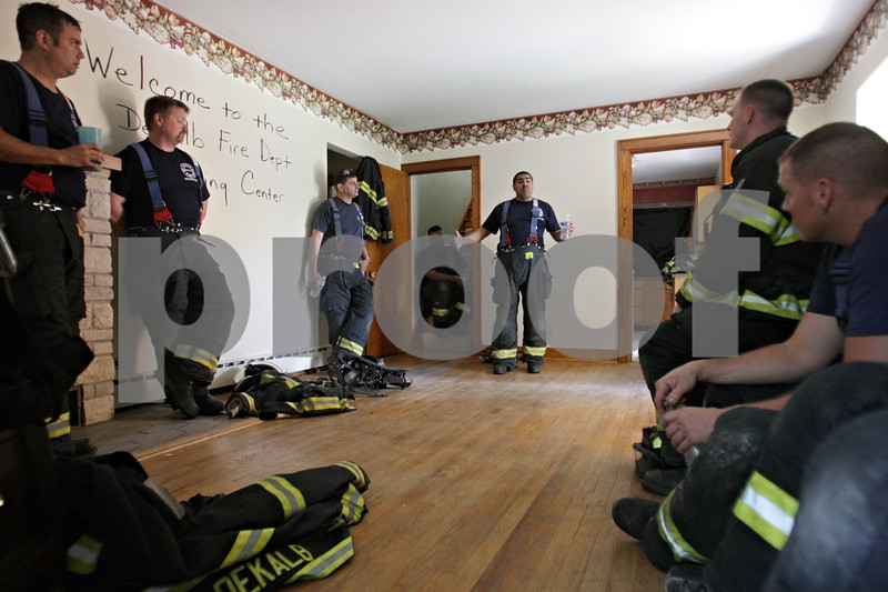 Rob Winner – rwinner@shawmedia.com<br /> <br /> Assistant Chief Jeff McMaster (center) of the DeKalb Fire Department briefs a group of firefighters between training exercises at an empty house located on Hollister Avenue in DeKalb, Ill., Wednesday, June 19, 2013.