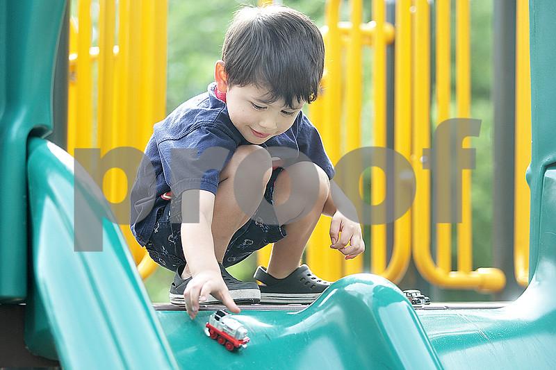 Monica Maschak - mmaschak@shawmedia.com<br /> Roberto Carrillo, 3, releases his toy trucks down a slide at Huntley Park in DeKalb on Monday, June 17, 2013.