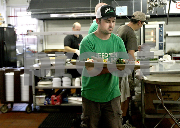 Monica Maschak - mmaschak@shawmedia.com<br /> Josh Akers leaves the kitchen with a tray of meals for customers at Feed 'em Soup in downtown DeKalb on Wednesday, June 26, 2013. The soup kitchen emits a restaurant feel, where the volunteers come around to tables to take the orders and serve the food.