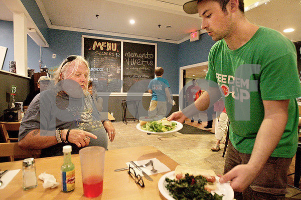Monica Maschak - mmaschak@shawmedia.com<br /> Volunteer Josh Akers (right) serves Jeff Cambell his food at Feed 'em Soup in downtown DeKalb on Wednesday, June 26, 2013. The soup kitchen emits a restaurant feel, where the volunteers come around to tables to take the orders and serve the food. Feed 'em Soup is open for dinner ever Wednesday.