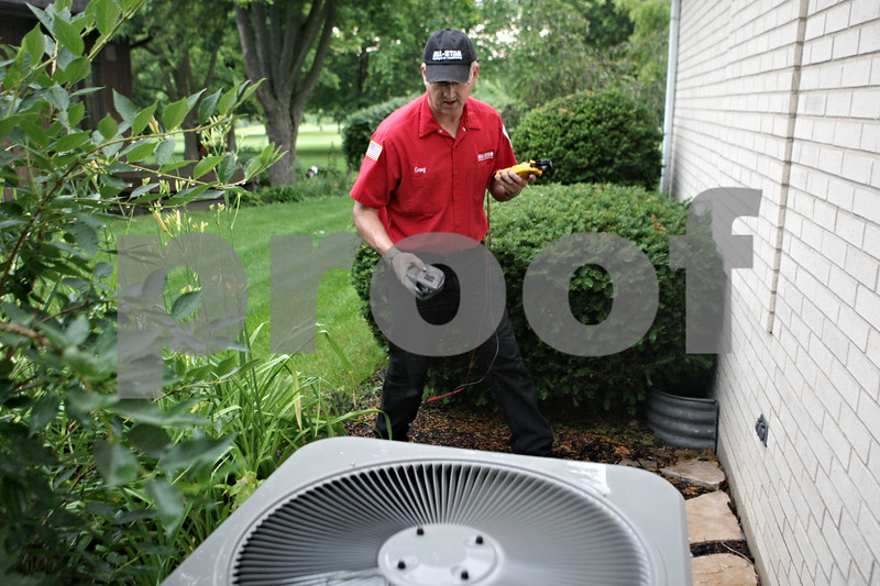 Rob Winner – rwinner@shawmedia.com<br /> <br /> Gregory Freeman owner of All-Star Heating and Air Conditioning uses a meter to check the electrical components of an air conditioner while performing a tune-up on the unit at a home in DeKalb on Tuesday, June 25, 2013.