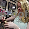 Lacey McKenzie adjusts a timepiece available for sale at Poppyseed Primitives. The store recently opened in its new DeKalb location. McKenzie said she sometimes helps owner Sandy Spier with the store.