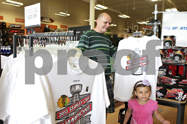 Rob Winner – rwinner@shawmedia.com<br /> <br /> DeKalb resident John Swanberg chooses a 2013 Stanley Cup Championship t-shirt while shopping for Chicago Blackhawks gear at MC Sports in DeKalb on Tuesday, June 25, 2013. The Blackhawks defeated the Boston Bruins, 3-2, in game six of the NHL Stanley Cup Final to clinch the championship on Monday night.