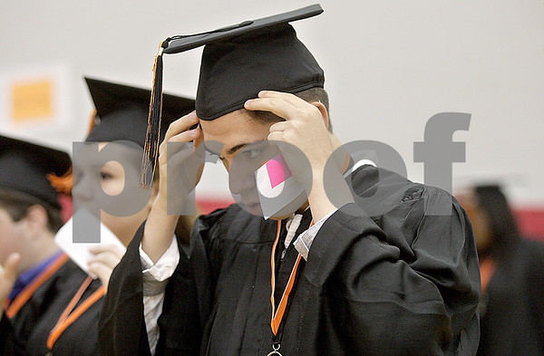 Monica Maschak - mmaschak@shawmedia.com<br /> Dan Guillotte places his cap on his head in preparation for the procession before the DeKalb High School commencement ceremony at the Northern Illinois University Convocation Center on Saturday, June 8, 2013. About 350 students graduated.