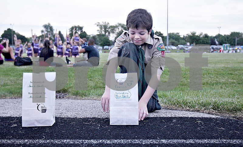 Monica Maschak - mmaschak@shawmedia.com<br /> Kenny Brown, 13, with Boy Scout troop 16, places a luminaria for his great-grandmother around the running track during the 17th annual Relay for Life of DeKalb County at Sycamore High School on Friday, June 14, 2013. Brown's great-grandmother was in remission from breast cancer for more than 20 years. Survivors, caregivers and supporters walked and raised money from 6 p.m. Friday until 6 a.m. Saturday.