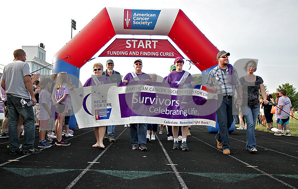 Monica Maschak - mmaschak@shawmedia.com<br /> Cancer survivors finish their survivors' lap and are joined by the caregivers for another lap during the 17th annual Relay for Life of DeKalb County at Sycamore High School on Friday, June 14, 2013. Survivors, caregivers and supporters walked and raised money from 6 p.m. Friday until 6 a.m. Saturday.