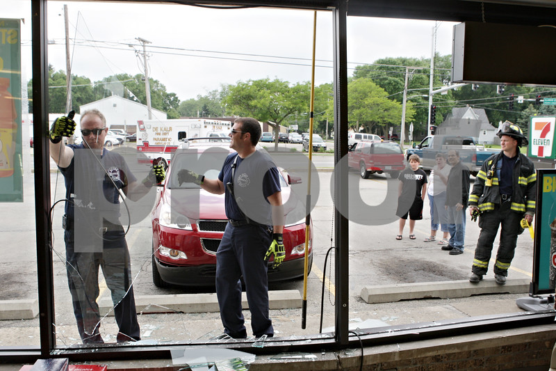 Rob Winner – rwinner@shawmedia.com<br /> <br /> DeKalb firefighters Tom Conley (left) and Greg Thornton remove broken glass from a frame after a Chevy Traverse crashed into the 7-Eleven storefront located at 802 S. Fourth Street in DeKalb, Ill., Monday, June 10, 2013.