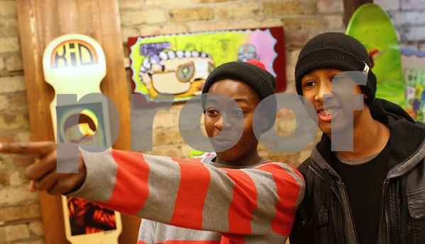 Kyle Bursaw — kbursaw@shawmedia.com<br /> <br /> Keire Johnson, 17 gets excited when he spots a piece of art with professional skateboarder Mark Gonzales on the wall, pointing it out to friend Steven Bailey-Murray, 15, as the two Rockford residents look around the sixth annual Skate Inspired Art Show at Smalltown Skate Shop in DeKalb, Ill. on Thursday, Feb. 28, 2013.