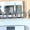 Kyle Bursaw – kbursaw@shawmedia.com<br /> <br /> Ashley and Tom Fawkes (reflected in microwave) look around their new kitchen as they do a final walk-through of the Cortland home with Maria Peña-Graham, their broker, on Monday, Feb. 25, 2013.