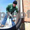 Kyle Bursaw – kbursaw@shawmedia.com<br /> <br /> Bob Dailey, an assistant tech with Radon Solutions, shakes brick debris from his drill as he works his way through the brick to run a pipe into the basement, part of the process of mitigating the radon in the Rockford, Ill. home on Wednesday, Feb. 20, 2013.