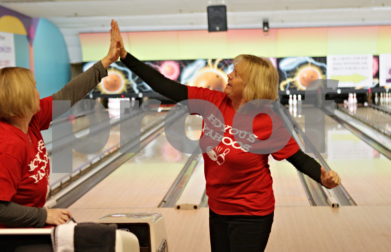 Rob Winner – rwinner@shawmedia.com<br /> <br /> Lori Phelps (center), a kindergarten teacher at Lincoln School in DeKalb, receives a high-five from fellow teacher Jamie Hartwig (left) during Friday night's Bowl for Kids' Sake event at Mardi Gras Lanes in DeKalb.