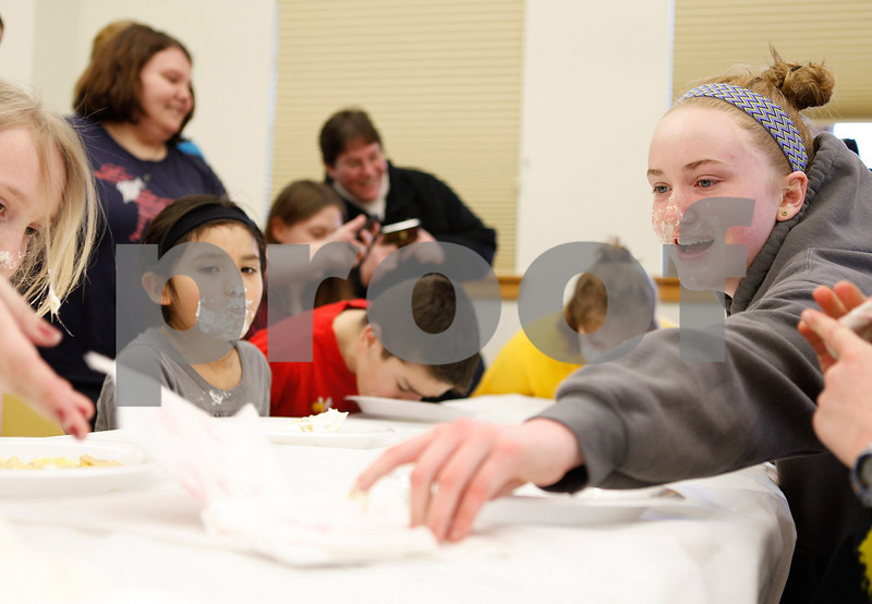 Erik Anderson - For the Daily Chronicle<br /> Libby Swedberg, 13, of Sycamore reaches for a napkin to wipe her face after finishing second place during the first round of the pie eating contest held at Sycamore Public Library in Sycamore on Thursday, March 14, 2013. The event was held to recognize Pi-Day or commonly known as (3.14).
