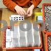 Kyle Bursaw – kbursaw@shawmedia.com<br /> <br /> Joe Becker fills packages with small pieces to be sent to the next station where they are sealed in the Opportunity House's workshop in Sycamore, Ill. on Thursday, March 7, 2013.