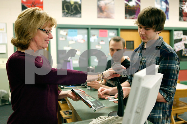 Erik Anderson - For the Daily Chronicle<br /> Librarian Deb Kreutziger checks out a book for juniors, Matt Baker (right) and Ryan Lindsey (left) in the library at Sycamore High School in Sycamore on Wednesday, March 13, 2013. After Deb checks out the book she will begin the physical processing of three new books to put on the library shelves.