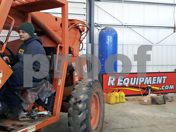 Shop technician Nathan Zeien works a forklift in the repair shop of R-Equipment in Sycamore.