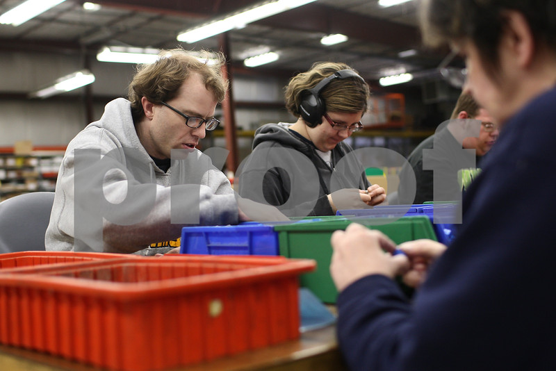 Kyle Bursaw – kbursaw@shawmedia.com<br /> <br /> Matt Rowan (left) and Brianne Mays (center) assemble small pieces with other workers in the Opportunity House's workshop in Sycamore, Ill. on Thursday, March 7, 2013.