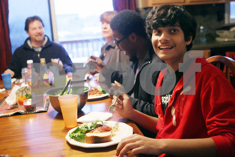 Rob Winner – rwinner@shawmedia.com<br /> <br /> Foreign exchange student Sharvil Patel (right), 15, sits down for dinner with the Wagnaar family of Cortland on Tuesday, March 12, 2013. Patel is the ninth exchange student the Wagnaar family has hosted.