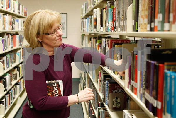 Erik Anderson - For the Daily Chronicle<br /> Librarian Deb Kreutziger organizes books and puts new books on the shelves in the library at Sycamore High School in Sycamore on Wednesday, March 13, 2013.