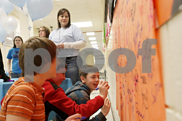 Rob Winner – rwinner@shawmedia.com<br /> <br /> (From front to back) AJ Petersen, 13, Chad Canaday, 13, and Jake Neidel finish signing their names on a poster to pledge to never use the word 'Retard' again in a derogatory manner at Clinton Rosette Middle School in DeKalb, Ill., Tuesday, March 19, 2013.