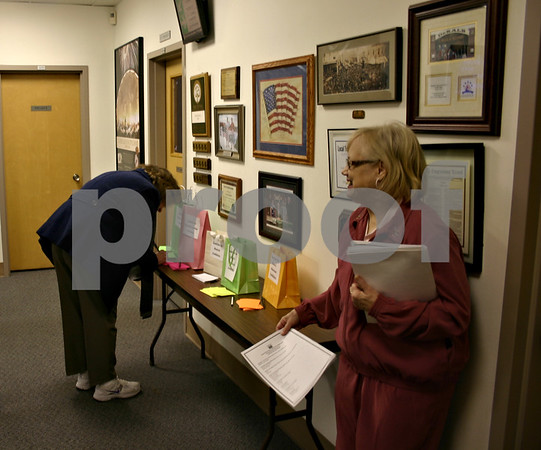 Jeff Engelhardt - jengelhardt@shawmedia.com<br /> Luanne Thorson hands out programs as attendees fill out questions for the DeKalb County League of Women Voters Candidates' Night at DeKalb City Hall Wednesday night.