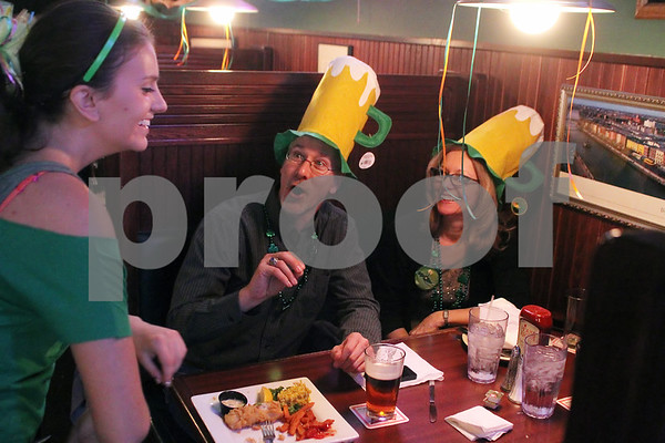 Downers Grove natives Kevin Frank (center) and Pat Scaccia (right) enjoy a laugh with O'Leary's Restaurant and Pub waitress Makaela Huerta during St. Patrick's Day festivities on Sunday.