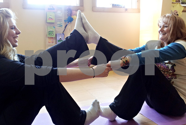 """David Thomas – dthomas@shawmedia.com<br /> <br /> Abby Knapek performs a """"double boat"""" with yoga instructor Sue Erickson (right). Erickson recently opened Katerpillar Kids Yoga in Sycamore, and is hosting three sessions at the Midwest Museum of Natural History in Sycamore later this month."""