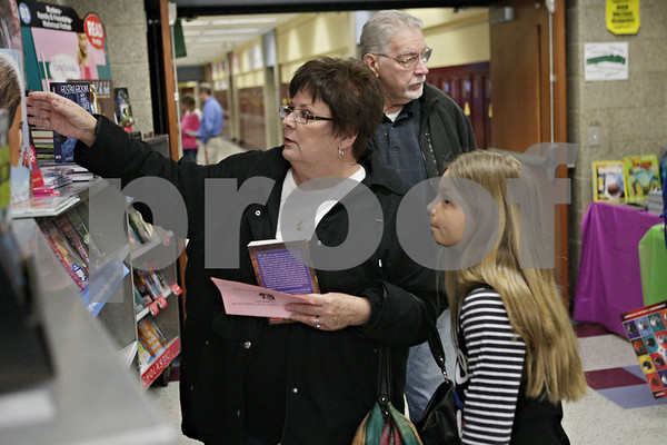 Rob Winner – rwinner@shawmedia.com<br /> <br /> Molly Snoke (left) and her granddaughter Olivia Mendiola, 9, look over books at a book fair as Stan Snoke looks on during Grandparents Day at Shabbona Elementary School on Friday, March 22, 2013.