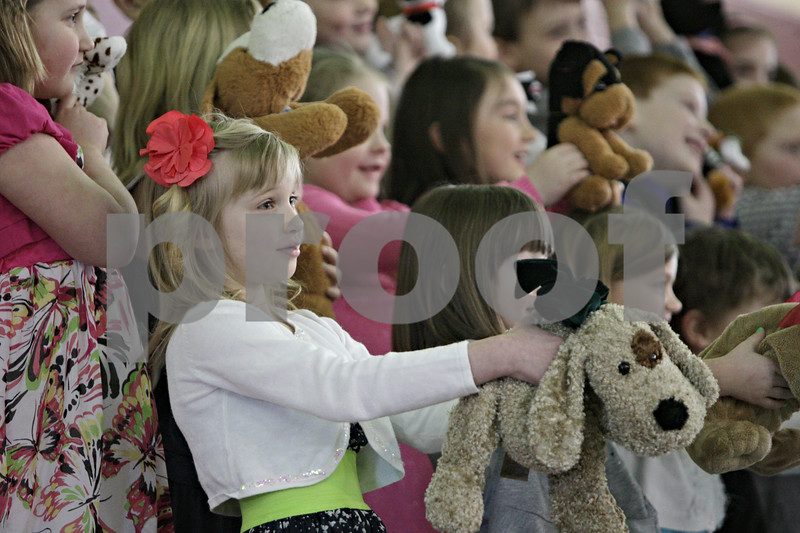 """Rob Winner – rwinner@shawmedia.com<br /> <br /> First grader Cheyenne Fay (front) holds up a stuffed animal dog while performing """"A Mud Puddle Jumped on Me!"""" during Friday morning's Grandparents Day at Shabbona Elementary School."""