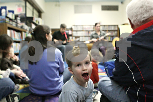 """Rob Winner – rwinner@shawmedia.com<br /> <br /> Three-year-old Isaac Smith, of DeKalb, looks back to his mother while reacting to the music of Nathan Dettman and Rebecca Hodson during story time  at the DeKalb Public Library on Tuesday, March 19, 2013. """"I want the snow to melt so it can be spring,"""" said Smith after learning that the theme of story time on Tuesday was all about spring."""