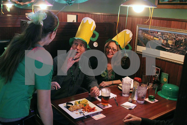 Downers Grove native Kevin Frank (center) gestures in fun to O'Leary's Restaurant and Pub waitress Makaela Huerta during St. Patrick's Day festivities on Sunday.  Friend Pat Scaccia looks on from his side.