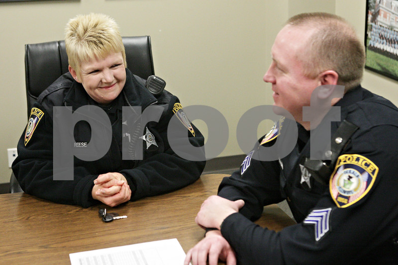 Rob Winner – rwinner@shawmedia.com<br /> <br /> Officer Reda Reese (left) listens as Sgt. Mark Tehan addresses fellow police officers during a roll call meeting at the DeKalb Police Department in DeKalb, Ill., Wednesday, March 20, 2013.
