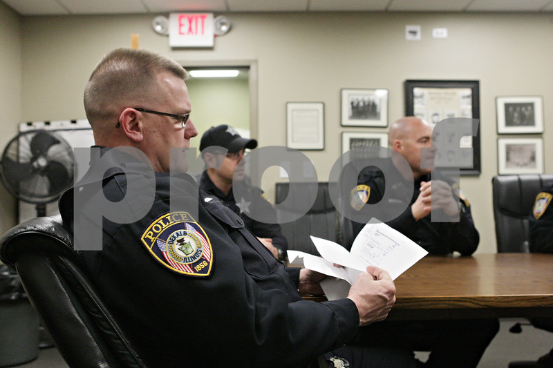 Rob Winner – rwinner@shawmedia.com<br /> <br /> Officer Burton Johnson (front) looks over some forgery case notes during an evening roll call meeting at the DeKalb Police Department in DeKalb, Ill., Wednesday, March 20, 2013.